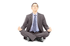 Young businessman in suit sitting on a floor and meditating. Isolated on white background Stock Photo