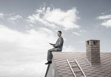 Student guy in suit on brick house roof reading book. Young businessman in suit sitting on house with red book in hands stock image