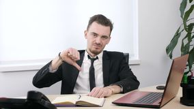 Young businessman in suit sitting in office and showing thumbs up sign 60 fps. 4k stock footage