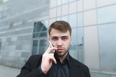 Young businessman in a suit talking on the phone and looking into the camera on the background of modern architecture. Royalty Free Stock Photography