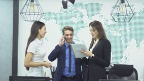 Business people working in office. Young businessman in suit talking on the phone and two young female employees discussing work in the office stock video