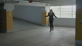 Young businessman in suit and tie going in the underground parking lot looking around and starting to dance funny -. Young businessman in suit and tie going in stock footage