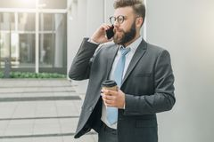Young businessman in suit and tie is standing outdoor, drinking coffee and talking on his cell phone.Man is working. Young businessman in suit and tie is Stock Photo
