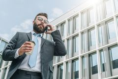 Young businessman in suit and tie is standing outdoor, drinking coffee and talking on his cell phone. In background is modern glass building. Man is working Stock Photos