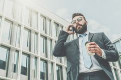 Young businessman in suit and tie is standing outdoor, drinking coffee and talking on his cell phone. In background is modern glass building. Man is working Royalty Free Stock Photos
