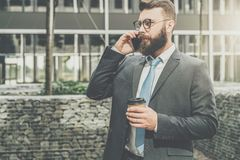 Young businessman in suit and tie is standing outdoor, drinking coffee and talking on his cell phone. In background is modern glass building. Man is working Stock Photo