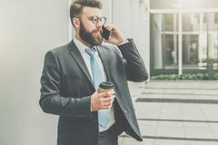 Young businessman in suit and tie is standing outdoor, drinking coffee and talking on his cell phone. In background is modern glass building. Man is working Stock Photography