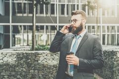 Young businessman in suit and tie is standing outdoor, drinking coffee and talking on his cell phone. In background is modern glass building. Man is working Royalty Free Stock Photo