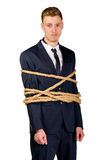Young businessman in a suit tied up. With rope Stock Photo