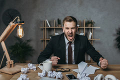 Young businessman in suit yelling while sitting at messy workplace. Angry young businessman in suit yelling while sitting at messy workplace stock image