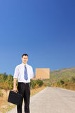 Young businessman with suitcase and cardboard hitchhiking on a r. Young businessman with suitcase and blank cardboard hitchhiking on a road Stock Images