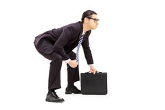 Young businessman in sumo wrestling stance holding suitcase Stock Image