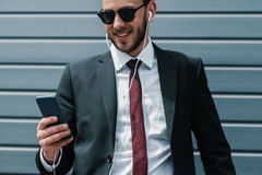 Young businessman in sunglasses and earphones using smartphone Stock Image