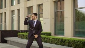Young businessman with sunglasses listening to the music on his smartphone outdoors and dancing. He walking near office. Building. Communication, audiobooks stock video footage