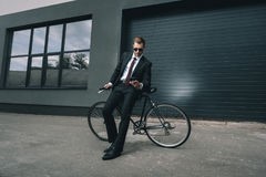 Young businessman in sunglasses sitting on bicycle and using smartphone Stock Photo