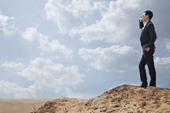 Young businessman in sunglasses standing in the desert and talking on the phone Royalty Free Stock Photos