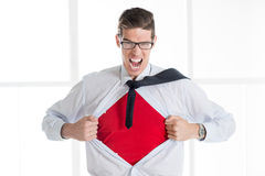 Young Businessman - Superhero. Angry businessman ripping open his shirt and exposing a Superhero red costume underneath. The man is wearing glasses and looking stock photo