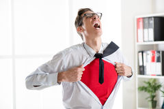 Young Businessman - Superhero. Angry businessman ripping open his shirt and exposing a Superhero red costume underneath. The man is wearing glasses stock photo