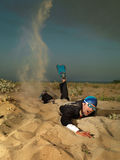 Young businessman swimming through sand in suit Stock Photo