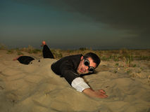 Young businessman swimming through sand in suit Stock Images
