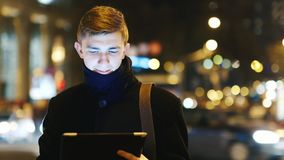Young businessman with the tablet against the night traffic stock footage