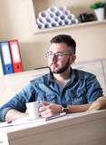 Young businessman taking coffee break in his office Royalty Free Stock Photo
