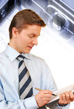 Young businessman taking notes. On a clipboard , cell keyboard in macro and light streaks on the background Stock Photo