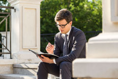 Young businessman taking notes. Handsome young businessman taking notes in notepad while sitting on stairs outside. Concrete columns and trees in the background Royalty Free Stock Images
