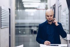 Young businessman taking thought cellphone in the office royalty free stock photo