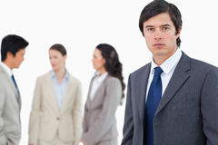Young businessman with talking associates. Behind him against a white background Stock Image