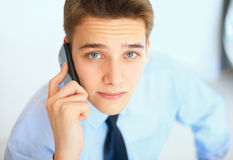 Young businessman talking on cell phone Royalty Free Stock Image