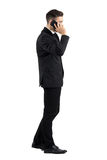 Young businessman talking on the cell phone walking side view Stock Images