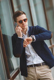 Young businessman talking on cellphone outdoors. Business young man,dark short hair,dressed in a white shirt,dark blue jacket and light brown pants with a waist Royalty Free Stock Photo
