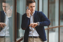 Young businessman talking on cellphone outdoors. Business young man,dark short hair,dressed in a white shirt,dark blue jacket and light brown pants with a waist Stock Image