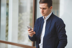 Young businessman talking on cellphone outdoors. Business young man,dark short hair,dressed in a white shirt,dark blue jacket and light brown pants with a waist Stock Photography