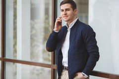 Young businessman talking on cellphone outdoors. Business young man,dark short hair,dressed in a white shirt,dark blue jacket and light brown pants with a waist Stock Images