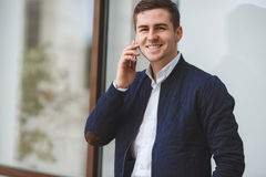 Young businessman talking on cellphone outdoors. Business young man,dark short hair,dressed in a white shirt,dark blue jacket and light brown pants with a waist Royalty Free Stock Image