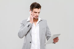 Young businessman talking on cellphone and using tablet Royalty Free Stock Images