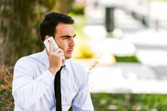 Young businessman talking on cellphone. Young business man talking on cellphone while sitting outdoor at bench - avenue Royalty Free Stock Photo