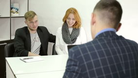 Young businessman talking with clients at office.