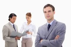Young businessman with talking colleagues behind him Royalty Free Stock Photography