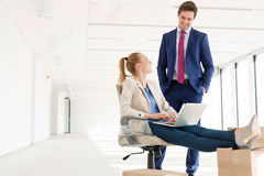 Young businessman talking with female colleague using laptop in new office Royalty Free Stock Photos