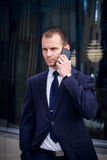 Young businessman talking on his cellphone. Against office building Stock Images