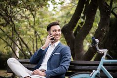 Young businessman talking on smartphone outdoors in a park. A young businessman talking on his smartphone outdoors in a park, sitting on a bench Royalty Free Stock Image