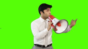 Young businessman talking into a megaphone on green background stock footage
