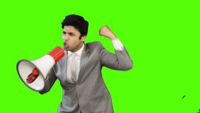 Young businessman talking into a megaphone on green background stock video