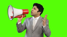 Young businessman talking into a megaphone on green background