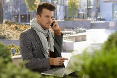 Young businessman talking on mobile outdoors. Young businessman sitting in citypark using mobilephone and laptop Royalty Free Stock Photos
