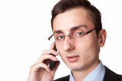 Young businessman talking on the mobile phone. On a white background. Taken close up Stock Photo