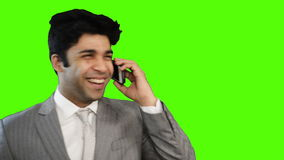 Young businessman talking on mobile phone against green background stock video